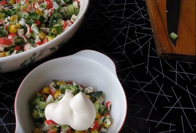 Salad of crab sticks with corn, cucumber, eggs and vegetables.