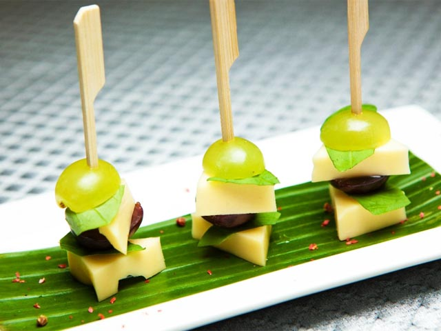 Canapés on skewers on the festive table.